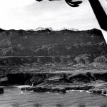 """Vista aérea del campo de vuelo de Llanes con los picos al fondo y se aprecia el Naranjo de Bulnes, desde la avioneta Fieseler """"storch"""" Conocida como Cigüeña"""
